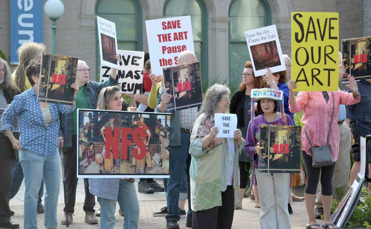 About 40 people opposed to the selling of The Berkshire Museum's art to fund an expansion and endowment, protest in front of museum in Pittsfield, Mass. on Saturday, Aug. 12, 2017. Some of the works on the auction block include original paintings by Norman Rockwell, a resident of The Berkshires, who gifted the art to the museum decades ago. (Gillian Jones/The Berkshire Eagle via AP) ORG XMIT: MAPIT101