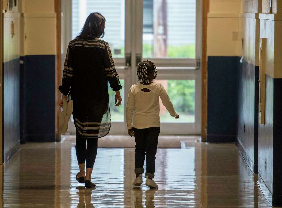 A student walks with a teacher through the hallway on the first day of school at the Lake Avenue Elementary School on Wednesday, Sept. 6, 2017, in Saratoga Springs, N.Y. (Skip Dickstein/Times Union) Photo: SKIP DICKSTEIN, Albany Times Union