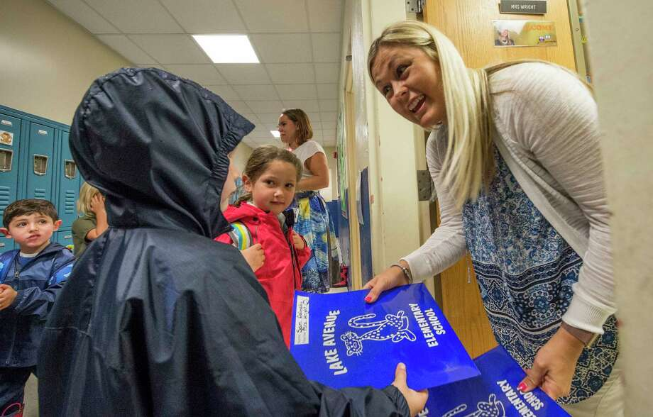 Take a look through the slideshow above of photos of first days of school in past years by Times Union photographers.  Kindergarten teacher Tara Wright welcomes one of her students on the first day of school at the Lake Avenue Elementary School on Wednesday, Sept. 6, 2017, in Saratoga Springs, N.Y. (Skip Dickstein/Times Union) Photo: SKIP DICKSTEIN, Albany Times Union