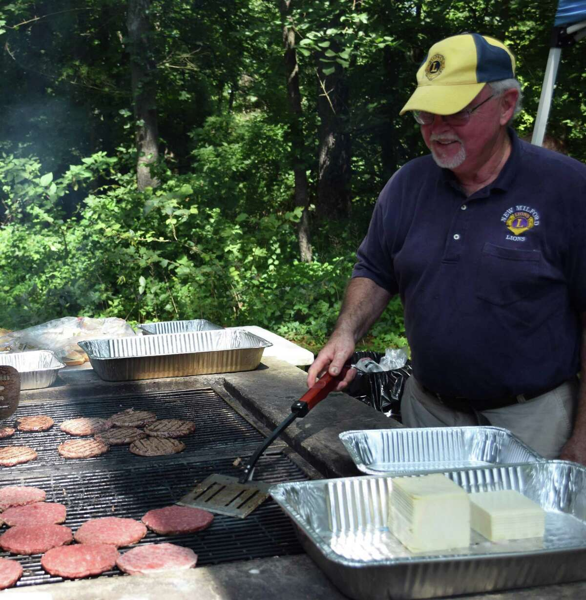 New Milford Lions Club president Jim Bannan oversees the grill as he and other Lions serve traditional picnic fare to local seniors.