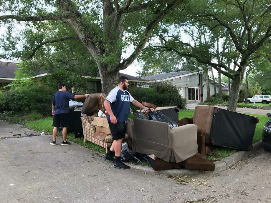 Joseph Dill helps clean up the house of four Rice football teammates that was flooded by Harvey.