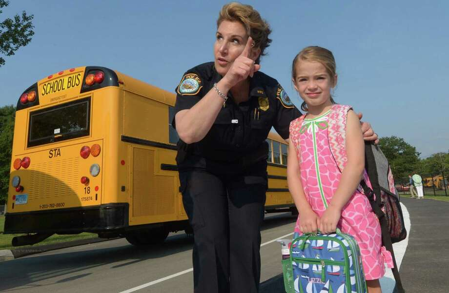 Wilton police officer Diane Maclean helps students including kindergartner Elizabeth Hubbard on their first day of class Photo: Erik Trautmann / Hearst Connecticut Media / Norwalk Hour
