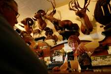 CCFOSTERSa-C-13MAR03-CF-MK --- Under the watchful eyes of 255 hunting trophies at Foster's Big Horn in Rio Vista, Alicia Quinday serves up a drink to a customer. BY MIKE KEPKA/THE CHRONICLE