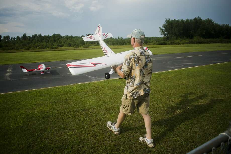 Jim Clark of Bentley carries his RC plane onto the runway before flying it during the Midland RC Club's new pilot training night on Monday, July 31, 2017 at the club's flying field, located on Patterson  Road between Ashby Road and Pine River Road in Midland. Photo: (Katy Kildee/kkildee@mdn.net)