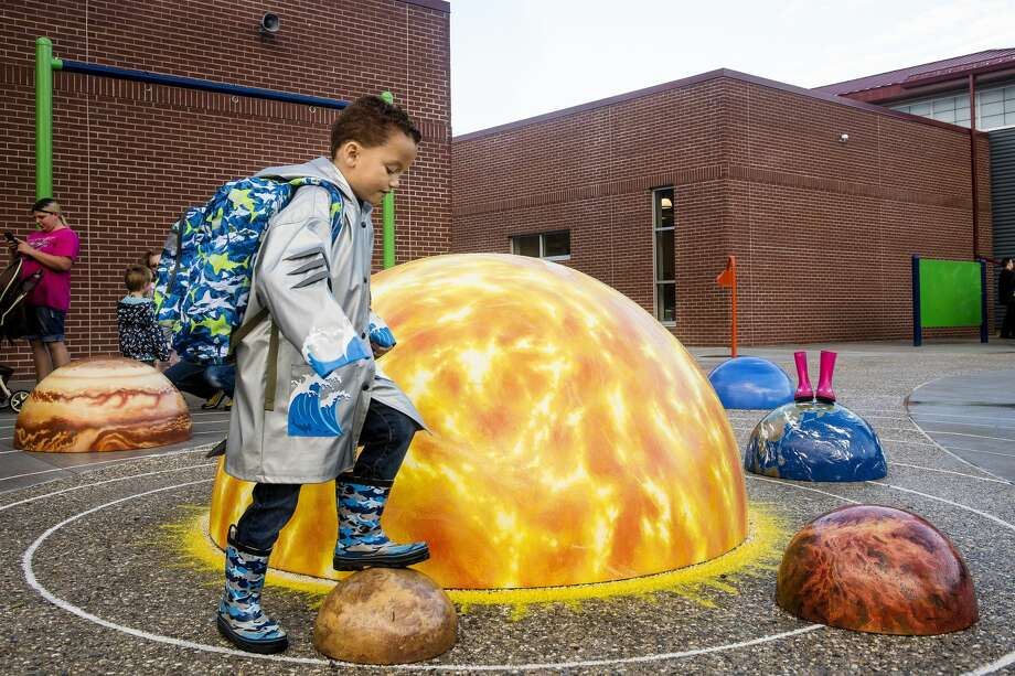 "First-grader Chase Riley, 6, steps over Mercury, part of a three-dimensional outdoor learning environment, during the first day of class in Central Park Elementary School on Tuesday.  ""I'm super excited. I love the new school,"" said Chase's mother, Dannye Riley. Photo: (Danielle McGrew Tenbusch/for The Daily News)"