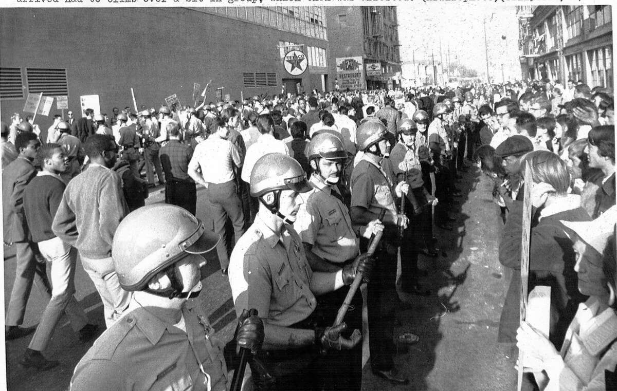 Police for two lines to enable the inductees to pass between the anti-war demonstrator sits in the street blocking access to the Oakland Induction Center , October 16, 1967 Vietnam War protesters Associated Press