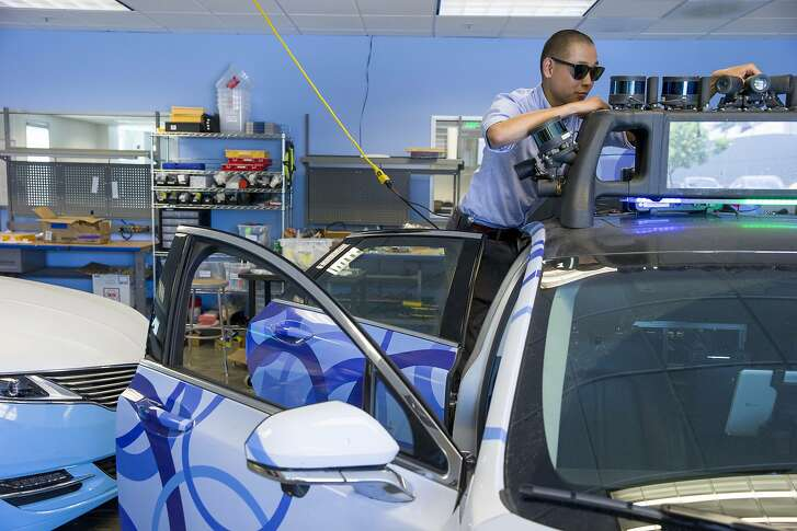Technician Joe Fey checks the sensors on the self driving car at drive.ai on Wednesday, Aug. 9, 2017, in Mountain View, Calif. Drive.ai is a Silicon Valley startup that's creating artificial intelligence software for autonomous vehicles.