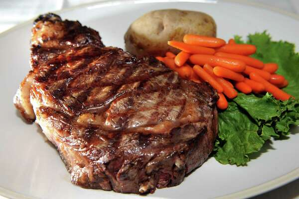 The Original Bears' Steak is a Delmonico steak served with a baked potato and carrots on Friday, Nov. 7, 2014, at The Bears' Steakhouse in Duanesburg, N.Y. (Cindy Schultz / Times Union)