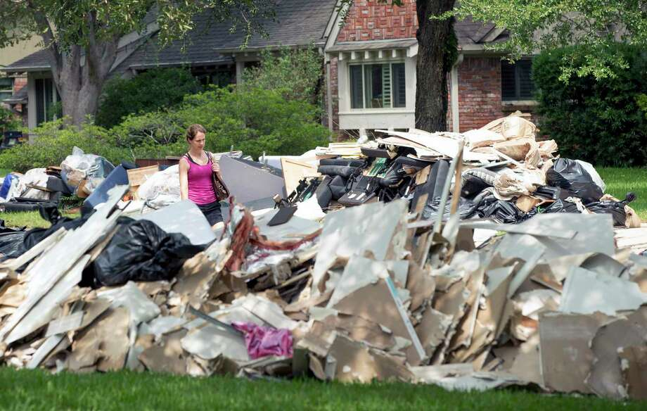 Paige Maupin walks in Meyerland near her brother's flood-damaged home. Photo: Jay Janner, Associated Press / Austin American-Statesman