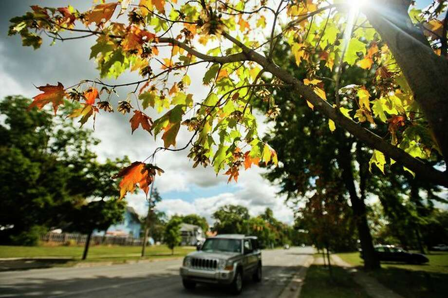 A vehicle drives along Indian Street as trees along the road begin to show fall colors on Wednesday. (Katy Kildee/kkildee@mdn.net)