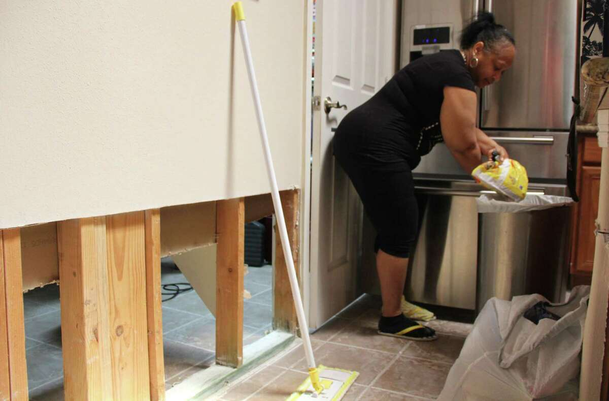 Alice Riley, resident of Canyon Village at Cypress Springs, cleans out her refrigerator on Sept. 5. Due to the floodwaters of Harvey, Riley lost most of the items in her home.