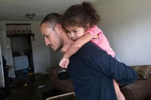 Byron Soto, de 31 años, ayuda a su hija Kiara a salir del apartamento que esta familia de inmigrantes tuvo que abandonar debido a las inundaciones en Houston. (Marie D. De Jesús / Houston Chronicle)
