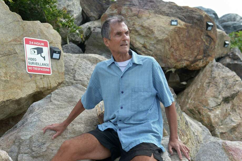Norwalk resident Tom Jankovic stands at the end of Shady Beach Saturday, September 2, 2017, where new signs and security cameras have been place on the breakwater there in Norwalk, Conn. Jankovic has been running from his home to Shady Beach at least once a week for the past 40 years and after his run and a brief swim would like to dry off on the breakwater at the end of the beach before running back. However, the adjoining property owner has recently put the breakwater under surveillance leading to controversy about whether beachgoers have the right to sit there. Photo: Erik Trautmann / Hearst Connecticut Media / Norwalk Hour