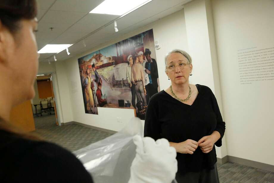 Catherine Powell (right), director of the labor archives and research center at San Francisco State University, discusses the Victor Arnautoff exhibit with Bianca Alper in the gallery where the university will showcase it. Photo: Lea Suzuki, The Chronicle