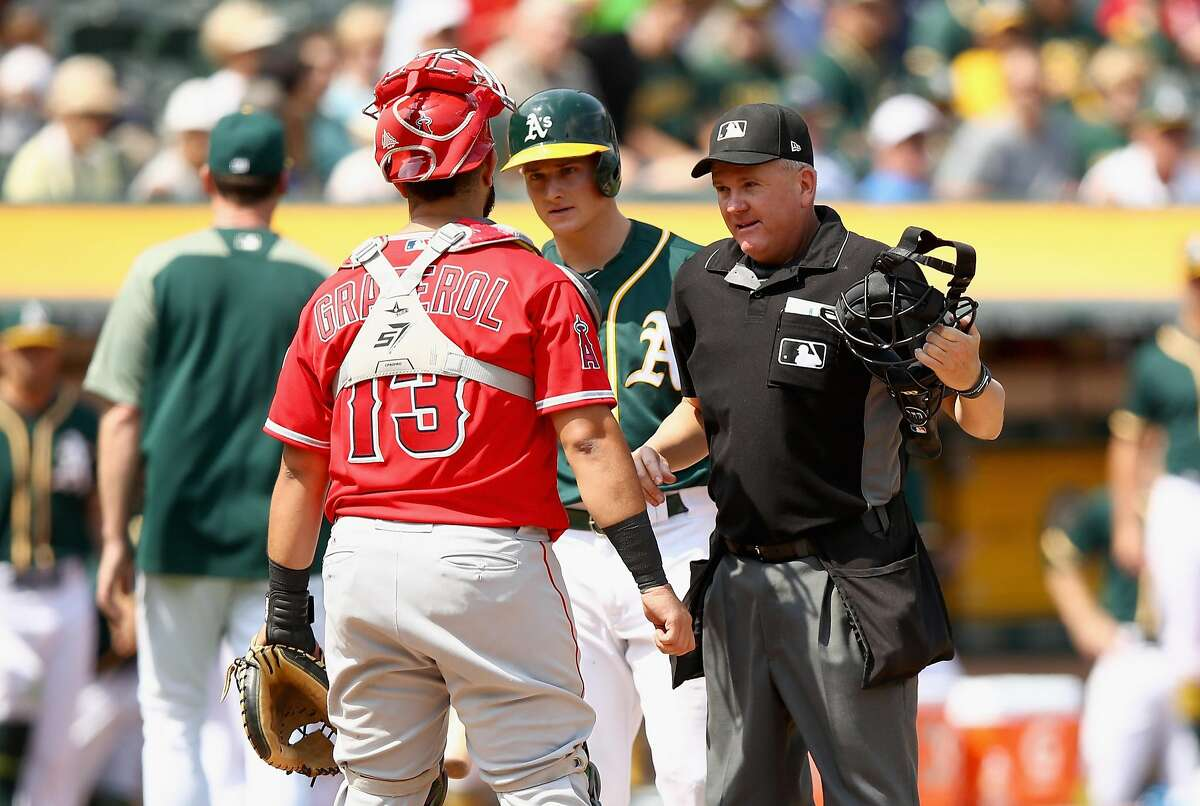 OAKLAND, CA - SEPTEMBER 06: Home plate umpire Mike Everitt stands in between Matt Chapman #26 of the Oakland Athletics and Juan Graterol #13 of the Los Angeles Angels in the fourth inning at Oakland Alameda Coliseum on September 6, 2017 in Oakland, California. Chapman was ejected on the play. (Photo by Ezra Shaw/Getty Images)