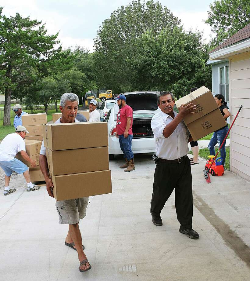 Church members at Casa De Oracion Cristiana on CR 4881 in Dayton help bring in supplies brought to them by Pct. 4 workers and Commissioner Leon Wilson. Photo: David Taylor
