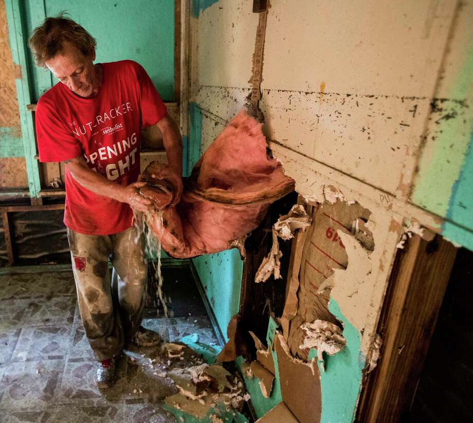 Thomas George, Jr., wrings water from the insulation of his home heavily damaged by floodwaters from Tropical Storm Harvey on Tuesday, Sept. 5, 2017, in Patton Village, Texas. The water line from the flood can be seen on the wall at hi shoulders. Photo: Brett Coomer, Houston Chronicle / © 2017 Houston Chronicle