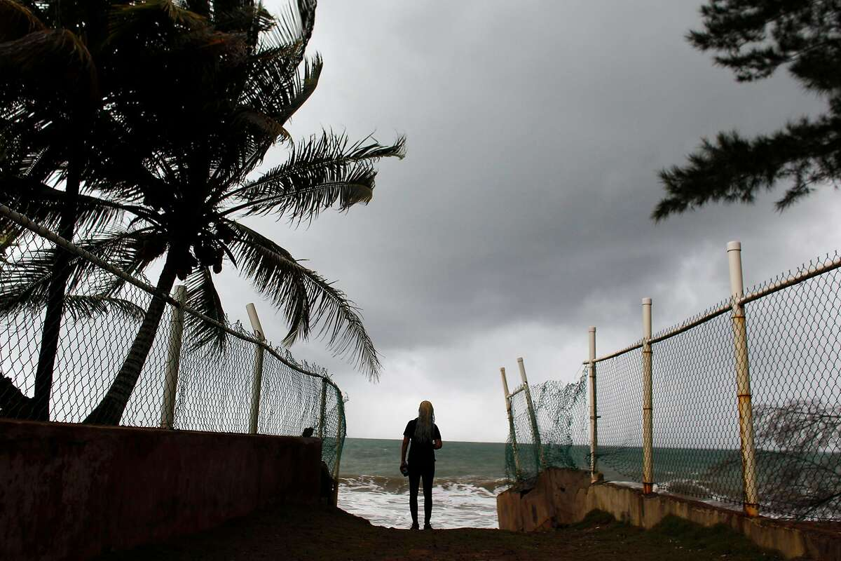 A woman looks at heavy surf as Hurricane Irma approaches Puerto Rico in Luquillo, on September 6, 2017. Irma is expected to reach the Virgin Islands and Puerto Rico by nightfall on September 6.