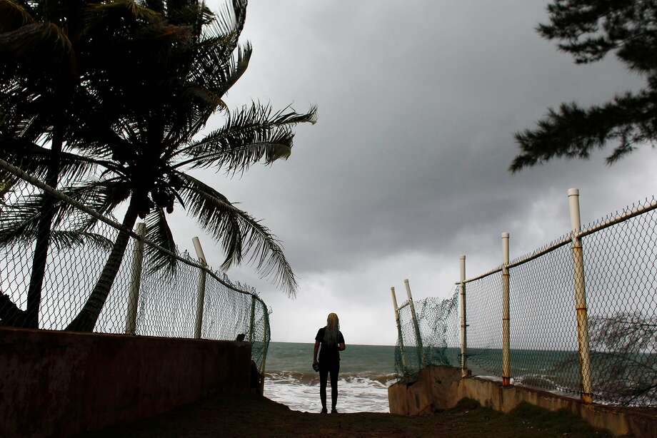 A woman looks at heavy surf as Hurricane Irma approaches Puerto Rico in Luquillo, on September 6, 2017. Irma is expected to reach the Virgin Islands and Puerto Rico by nightfall on September 6. Photo: RICARDO ARDUENGO, AFP/Getty Images