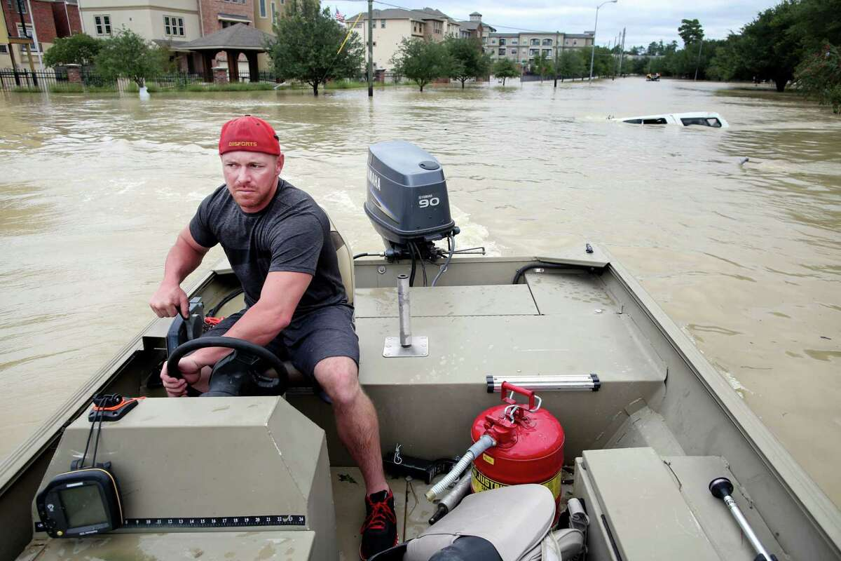 Jacob Wells pilots his boat through a flooded neighborhood in The Woodlands, north of Houston, on Wednesday, Aug. 30, 2017. Waters began to recede in parts of flood-ravaged Houston on Wednesday as Tropical Storm HarveyÂ?'s wrath shifted east. (Barbara Davidson/The New York Times)