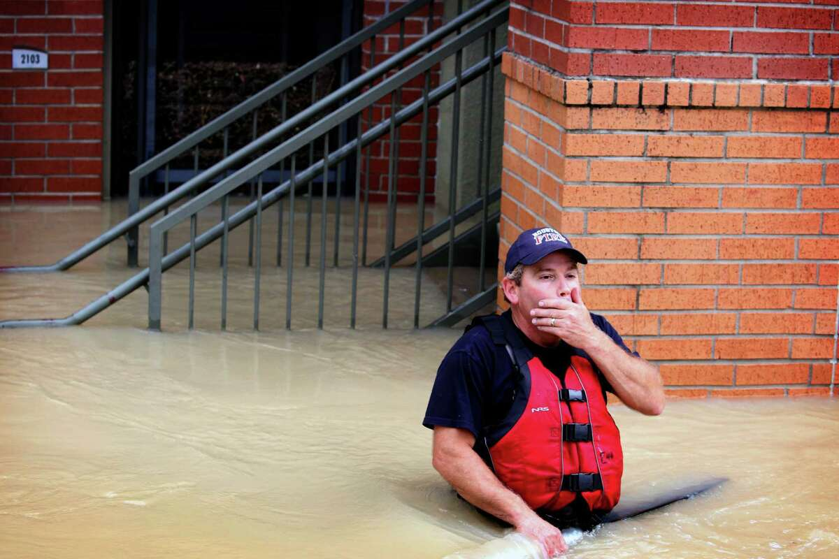 Houston firefighter Donnie McComb turns back to a waiting rescue boat after knocking on a door to follow up on a missing persons report in a flooded neighborhood in The Woodlands, north of Houston, on Wednesday, Aug. 30, 2017. Waters began to recede in parts of flood-ravaged Houston on Wednesday as Tropical Storm HarveyÂ?'s wrath shifted east. (Barbara Davidson/The New York Times)