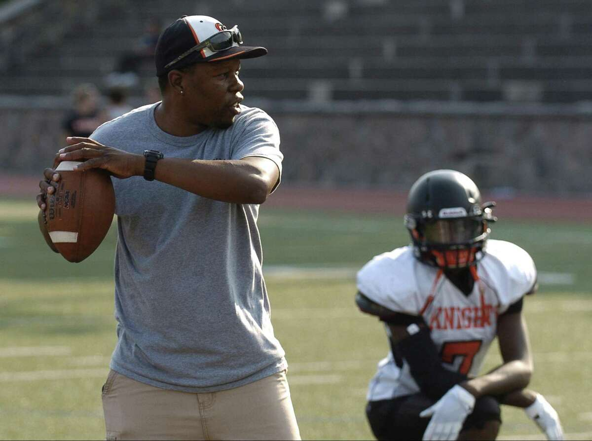 Stamford coach Jamar Greene throws to a receiver during a team practice at Stamford High School's Boyle Stadium in Stamford, Connecticut on Tuesday, Sept. 5, 2017.