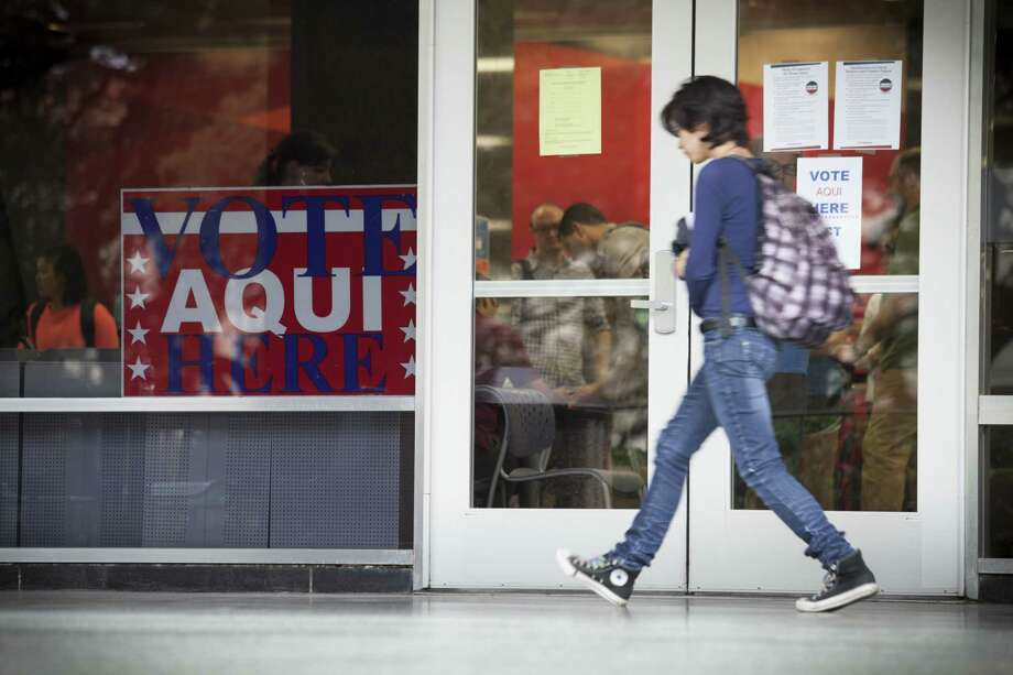 Voter ID requirements are posted outside a polling place on the University of Texas campus in Austin in this 2014 photo. The U.S. 5th Circuit Court of Appeals on Tuesday put on hold a lower court's decision blocking the state from enforcing a controversial voter ID law the Legislature passed this year. Photo: New York Times File Photo / NYTNS