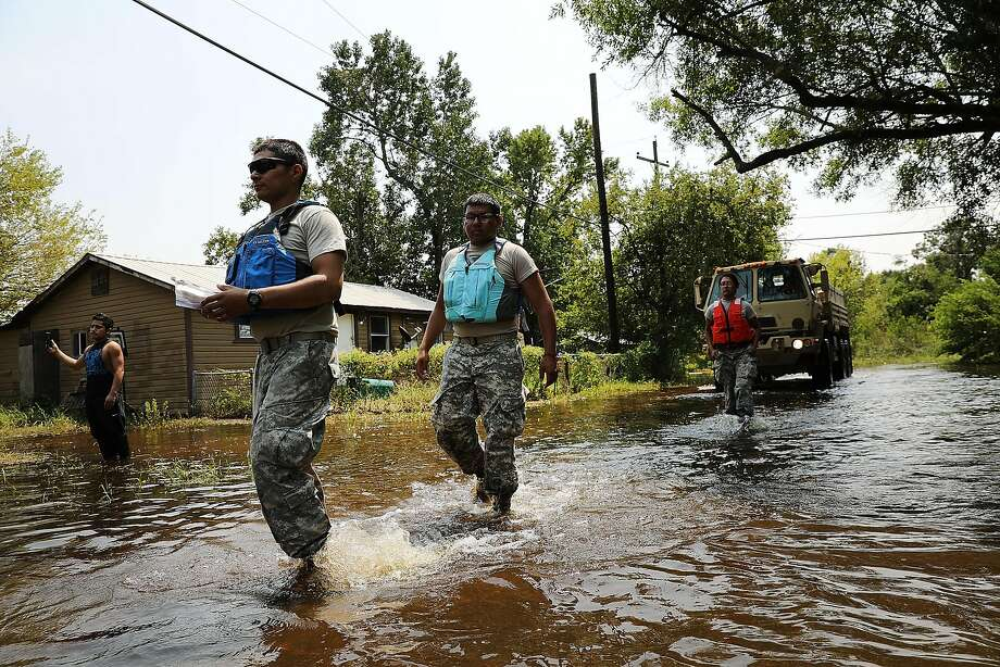 Members of the Texas National Guard distribute water and emergency meals in a remote neighborhood that was badly flooded by Hurricane Harvey. Photo: Spencer Platt, Getty Images