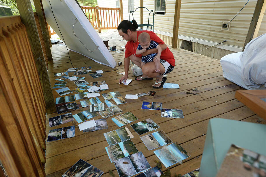 Samantha Johnson picks up pictures Wednesday that had been drying at her Kountze home. The Johnson property including homes and businesses was under several feet of water from Hurricane Harvey's flood waters. Photo taken Wednesday, September 06, 2017 Guiseppe Barranco/The Enterprise Photo: Guiseppe Barranco, Photo Editor / Guiseppe Barranco ©