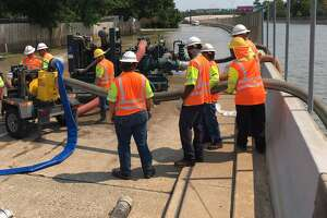 A Texas Department of Transportation crew uses a portable pump to bring water from the depressed section of the Sam Houston Tollway south of Interstate 10 to the frontage road, where it will flow to Buffalo Bayou on Wednesday.