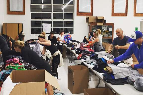 While Texans dig out from Hurricane Harvey flooding, volunteers with the Aid Cleveland Texas campaign in Manhattan Beach, Calif., put together clothing items to help flood victims. The items will be distributed Saturday, Sept. 9, at Cleveland High School.