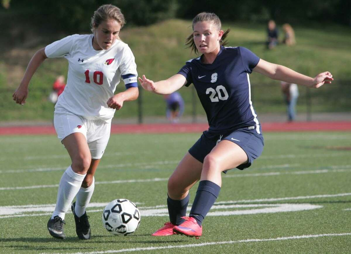 Greenwich's Emily Berzolla (10) brings the ball up field under pressure from Staples' Annie Amacker during a varsity girls soccer match in Greenwich on Friday, Sept. 25, 2015.