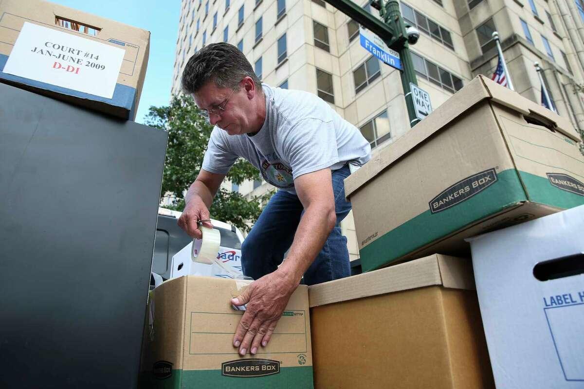 Investigator Bennie Cowey secures boxes that will be moved from the Harris County District Attorney's offices at the criminal courthouse on Franklin Street, which will be closed due to water damage. Story on page A10.