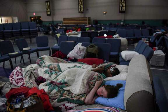 "Hurricane Harvey evacuees Stephanie and Nash Ubale sleep for the night at Calvary Community Church in Houston. The couple lost their home to flooding the same week they had a funeral for their newborn twins. ""We lost everything and more,"" they said. The couple are now thinking about moving out of the city. Must credit: Washington Post photo by Ricky Carioti"