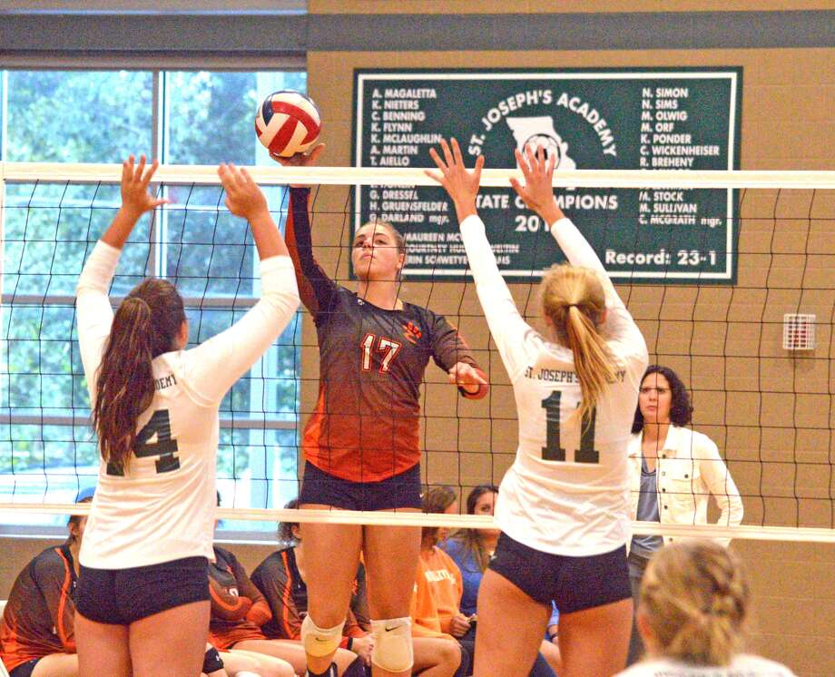 Edwardsville senior Rachel Pranger, middle, tries to hit over a pair of St. Joseph's Academy players during Wednesday's match at St. Joe's.