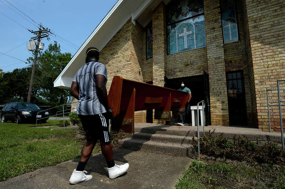 Jordan Benoit, left, and Camron Coleman move a damaged pew out of Magnolia Missionary Baptist Church on Pine Street in the north end of Beaumont on Wednesday.  Photo taken Wednesday 9/6/17 Ryan Pelham/The Enterprise Photo: Ryan Pelham / ©2017 The Beaumont Enterprise/Ryan Pelham