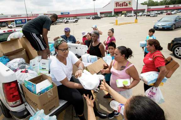 """People line up for free barbecue prepared by """"House of Hoops BBQ"""" near a storm-shuttered Fiesta Mart."""