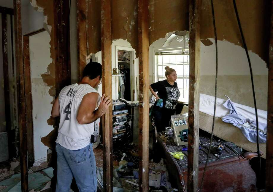 Rikki Saldivar, right, and her dad, Ric Saldivar, look at the damaged remains of a house that belonged to Ric Saldivar's parents, Sept. 5, 2017, in Houston. His parents and four young relatives drowned in a van in Greens Bayou during Tropical Storm Harvey.  ( Jon Shapley  / Houston Chronicle ) Photo: Jon Shapley, Staff / © 2017 Houston Chronicle