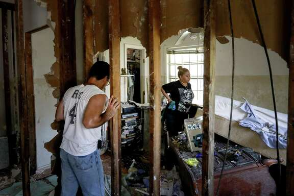 Rikki Saldivar, right, and her dad, Ric Saldivar, look at the damaged remains of a house that belonged to Ric Saldivar's parents, Sept. 5, 2017, in Houston. His parents and four young relatives drowned in a van in Greens Bayou during Tropical Storm Harvey.  ( Jon Shapley  / Houston Chronicle )