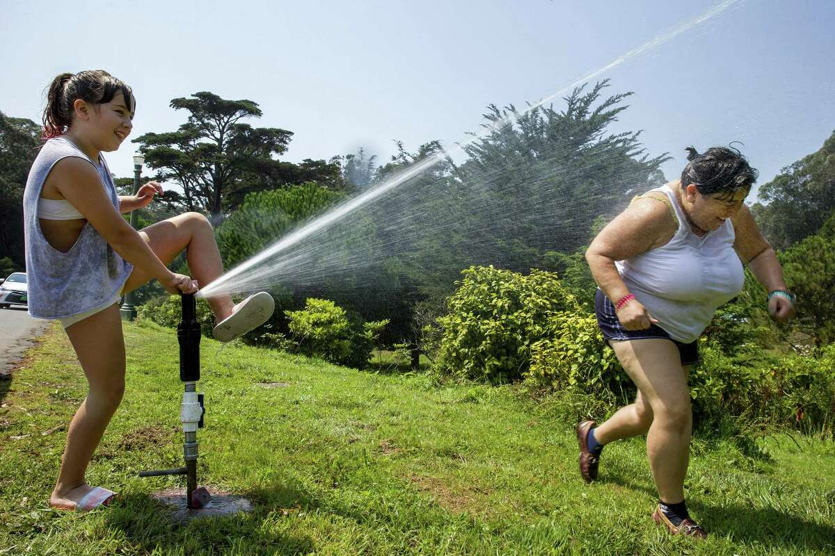Amilia Madigan, age 11, and her mother Desy Stoyanov cool off from the heat at Golden Gate Park in San Francisco, California on Friday, September 1, 2017.