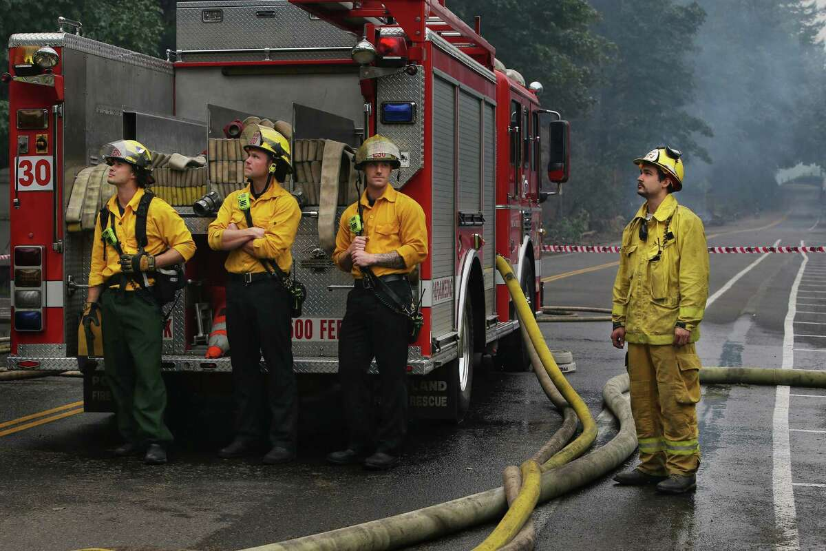 Firefighters look up towards Multnomah Falls after spending the past days protecting Multnomah Falls Lodge, which was built in 1925, from the Eagle Creek Fire, Wednesday, Sept 6, 2017, near Troutdale, Or. The lodge survived the worst of the fire, but hot spots continue to burn and trees continue to fall from the hills nearby.