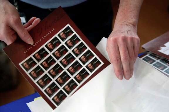 A U.S. Postal Service worker places a sleeve of Henry David Thoreau postage stamps in a bag. An analysis shows that the Postal Service could need to increase the cost of stamps to 60 cents.