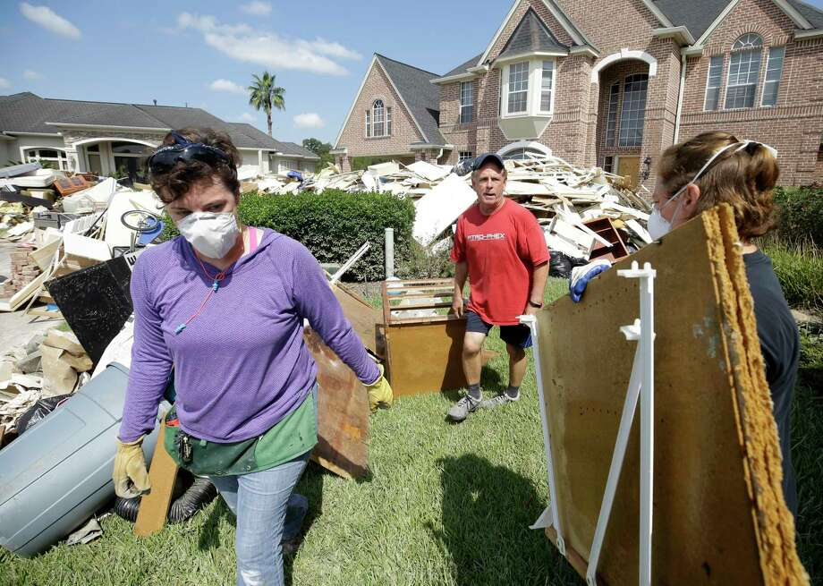 Tom Mayne, center, a member of Champion Forest Baptist, 15555 Stuebner Airline Rd., works with a crew from his church helping him with cleanup on Tuesday, Sept. 5, 2017. Photo: Melissa Phillip, Staff / © 2017 Houston Chronicle
