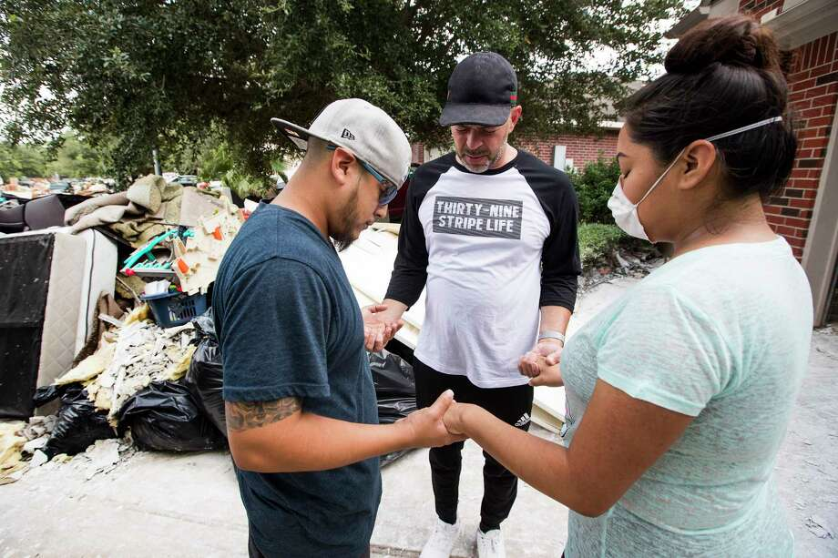 Juan Martinez, pastor of Get Wrapped Church, prays with Edwin and Berenice Gamino outside their home, that was flooded by Tropical Storm Harvey, as he delivers relief supplies with his parishioners on Tuesday, Sept. 5, 2017, in Spring. ( Brett Coomer / Houston Chronicle ) Photo: Brett Coomer, Staff / © 2017 Houston Chronicle