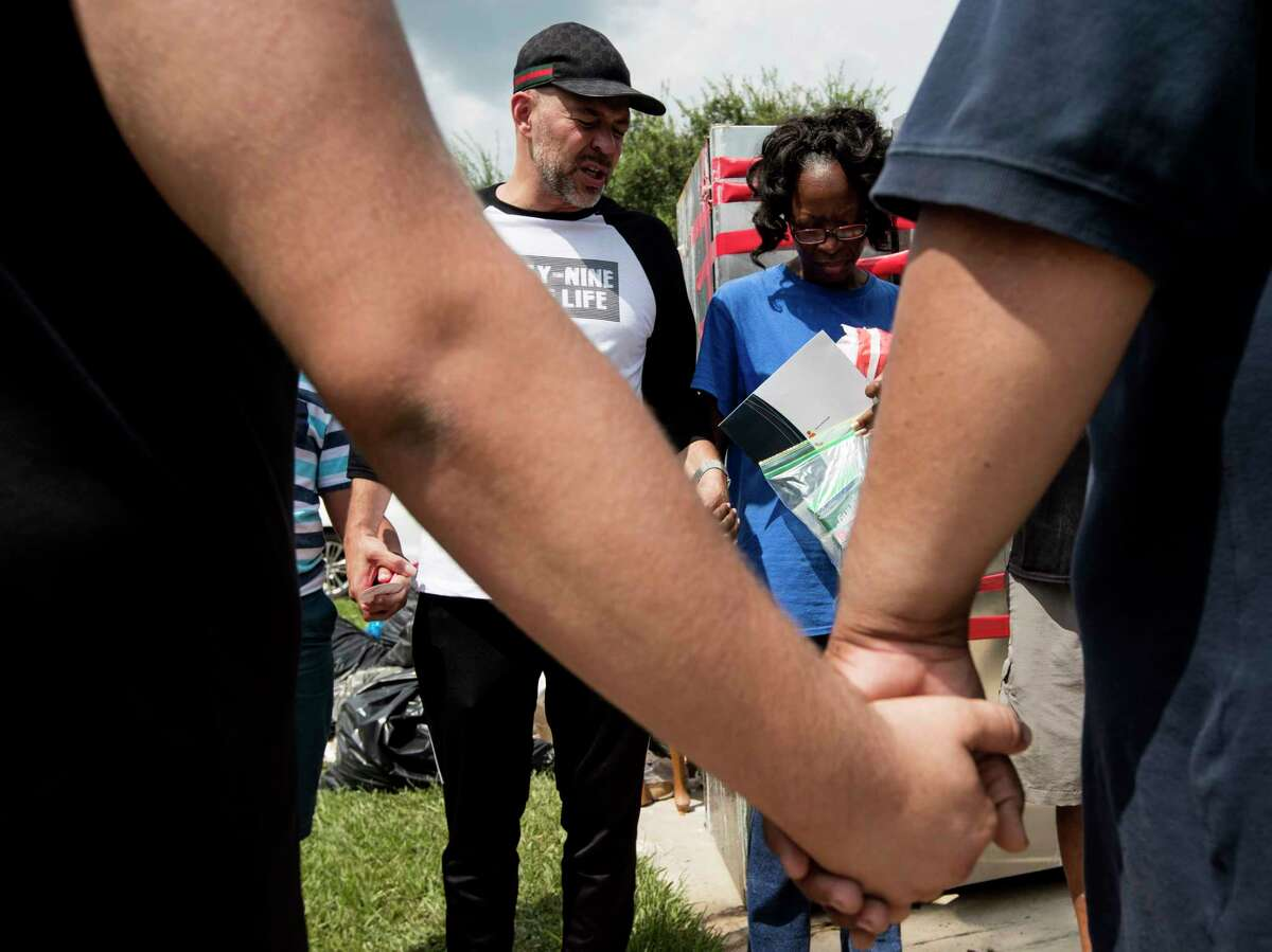 Juan Martinez, pastor of Get Wrapped Church, stands with Janice Dozier, whose home was flooded, as he gathers a group of his church members and victims of the flooding for a prayer on Tuesday, Sept. 5, 2017, in Spring.