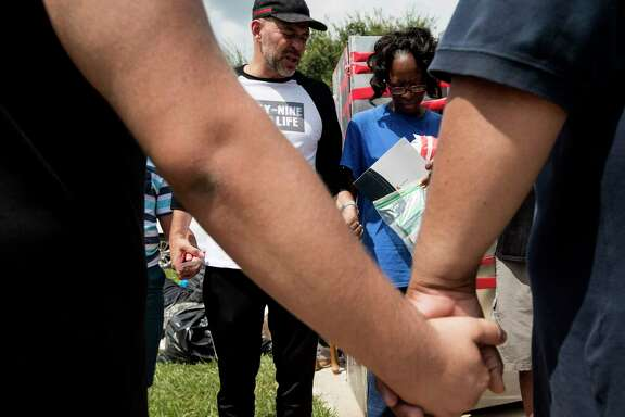 Juan Martinez, pastor of Get Wrapped Church, stands with Janice Dozier, whose home was flooded, as he gathers a group of his church members and victims of the flooding from Tropical Storm Harvey for a prayer on Tuesday, Sept. 5, 2017, in Spring. ( Brett Coomer / Houston Chronicle )