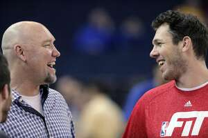 Warriors coach Luke Walton, right, talks with former Warrior and radio personality, Tom Tolbert before the Golden State Warriors played the Boston Celtics at Oracle Arena in Oakland, Calif., on Sunday, January 25, 2015. The Warriors won 114-111.