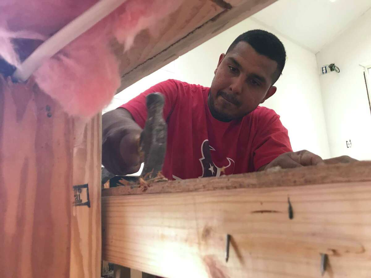 Roberto Vidales, an undocumented carpenter who came to the United States with his parents when he was a baby, works with a demolition crew to remove molding wood from a flooded home in Meyerland.
