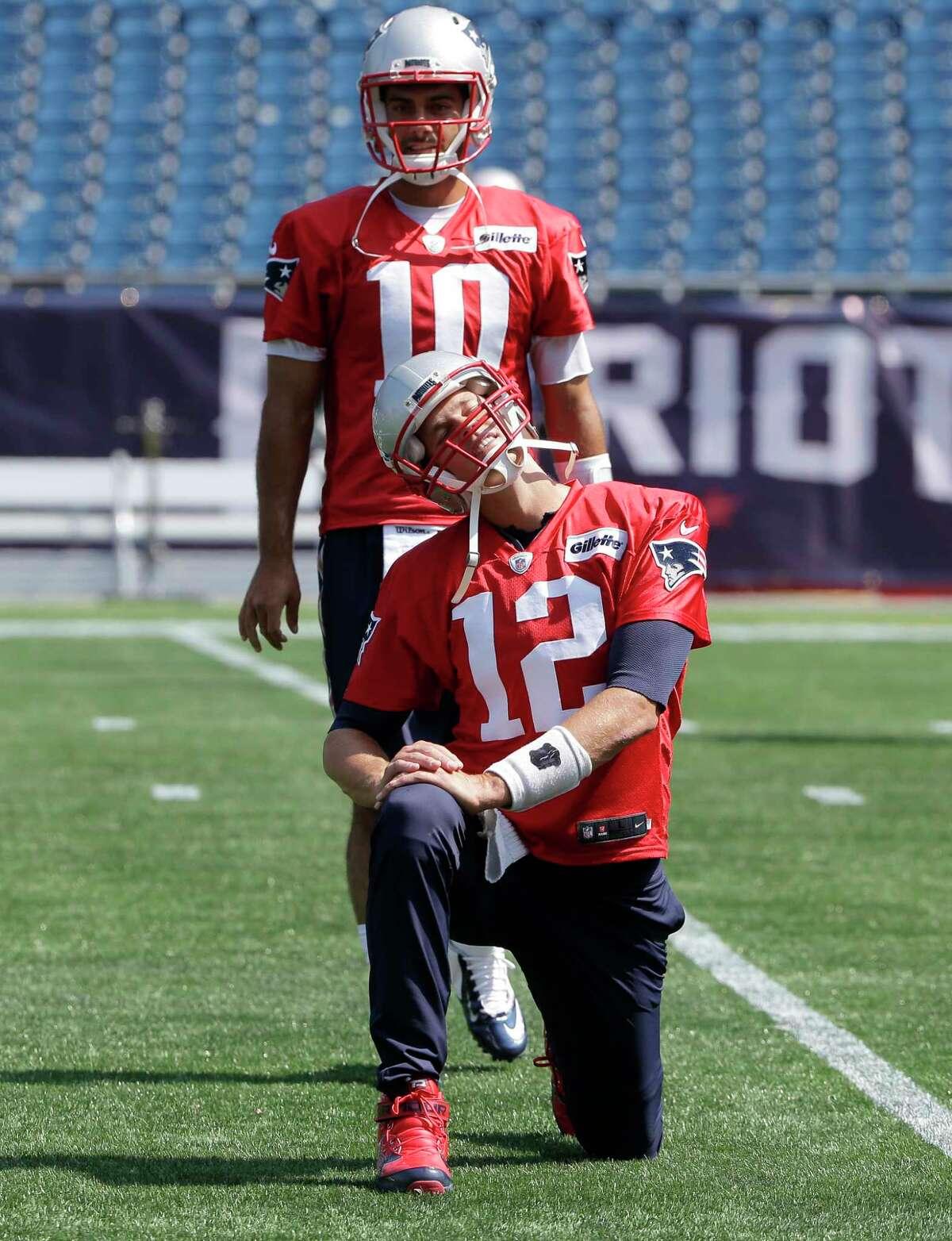 New England Patriots quarterbacks Tom Brady (12) and Jimmy Garoppolo (10) warm up during an NFL football practice, Tuesday, Sept. 5, 2017, in Foxborough, Mass. (AP Photo/Steven Senne) ORG XMIT: MASR101