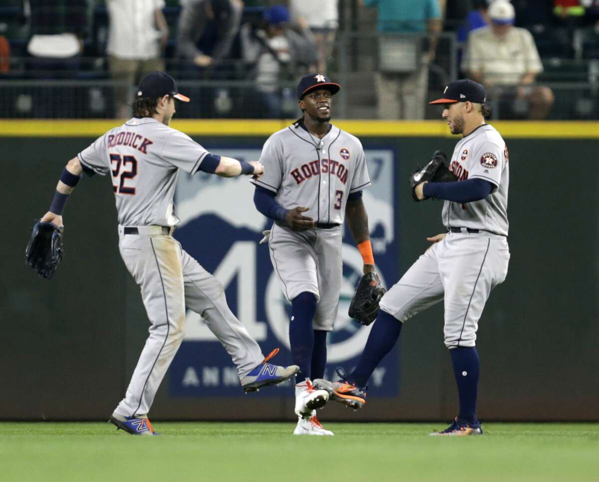 Houston Astros Josh Reddick, left, Cameron Maybin, center, and George Springer, right, celebrate a 5-3 win over the Seattle Mariners of a baseball game Wednesday, Sept. 6, 2017, in Seattle. (AP Photo/John Froschauer)